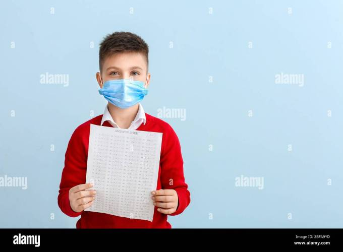 Pupil In Protective Mask And With Answer Sheet For School Test On Color Background Concept Of Epidemic Stock Photo Alamy