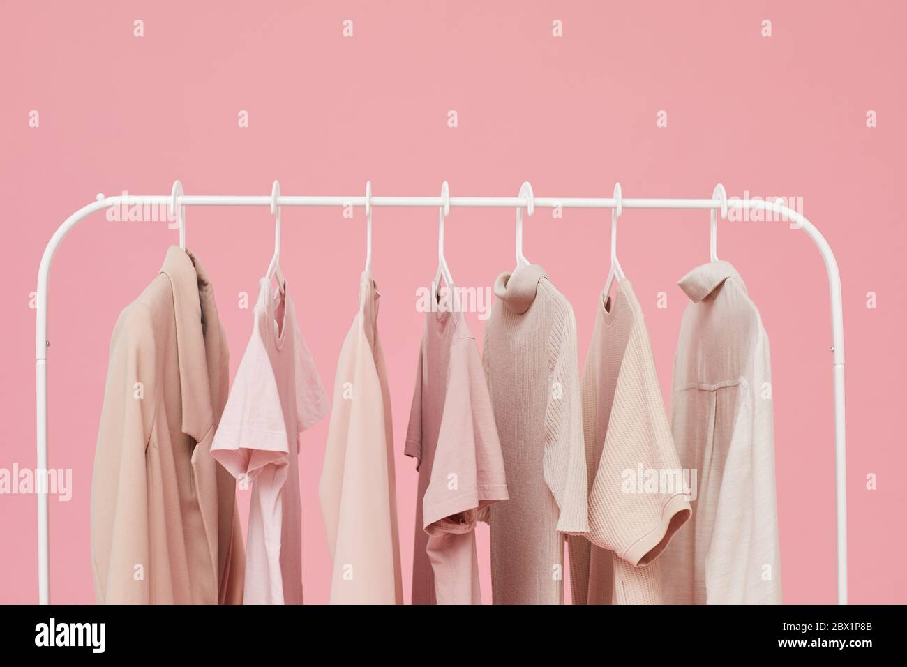 https www alamy com image of clothes hanging on the rack isolated on pink background image360227851 html