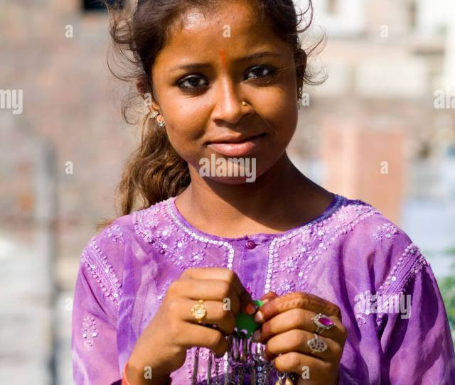 Beautiful Portrait Of Young Indian Girl Aged  In Purple In Front Of Village Of Jodhpur In Rajasthan India