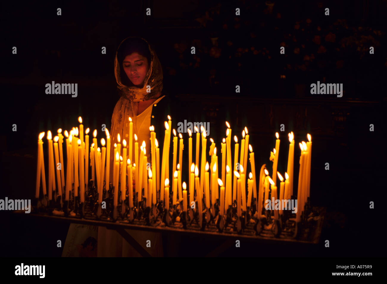 https www alamy com a woman lighting prayer candles inside a catholic church in italy image5658424 html