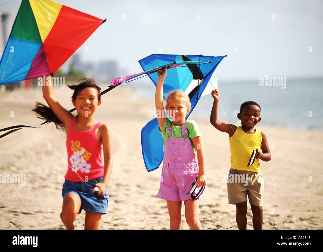 Children Age 6 Flying Kites On The Beach With Mixed Ethnic