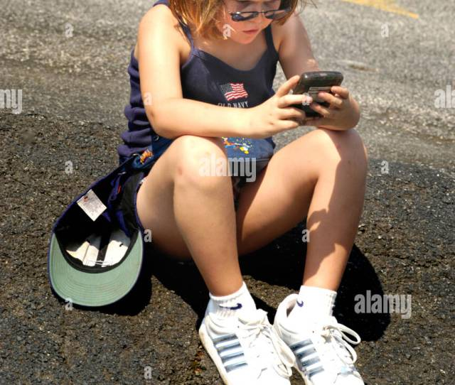 Young Girl Playing Game Boy Outside By Herself