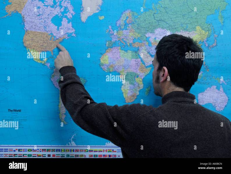 geography teacher pointing to United States on a world political map     geography teacher pointing to United States on a world political map