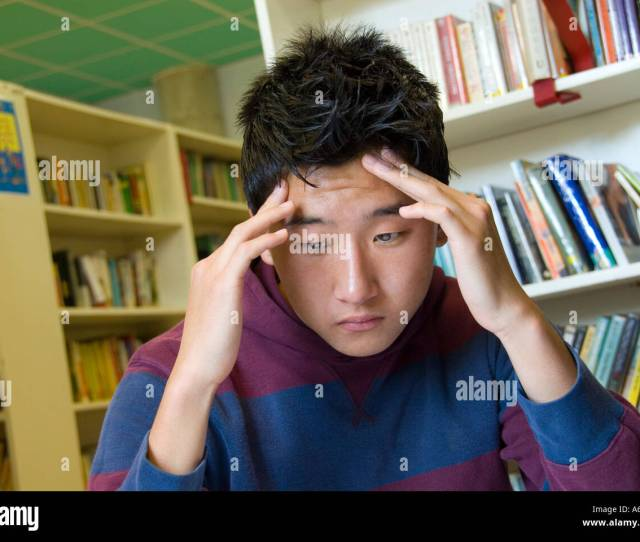 Oriental Teenage Boy Under Exam Time Pressure Concentrates Hard On His Exam Studies In School Library