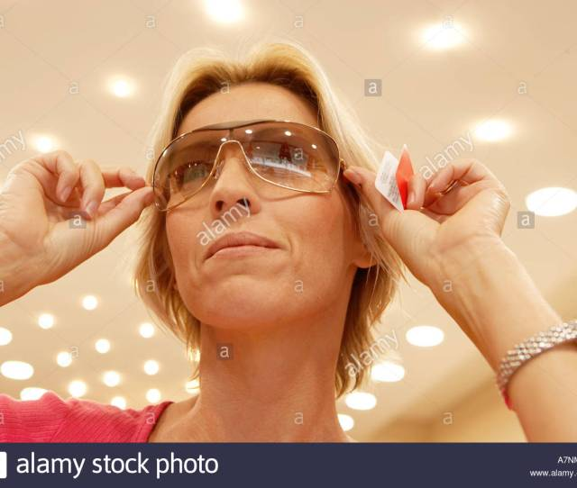 Mature Blonde Woman Trying On Pair Of Sunglasses In Shop Smiling Close Up Low Angle View