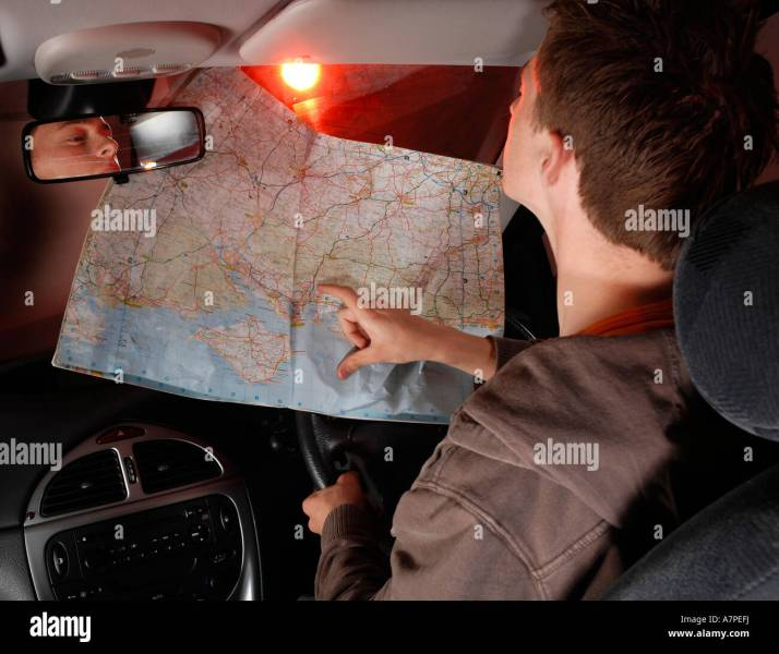 Young man reading a map while driving Stock Photo  11890325   Alamy Young man reading a map while driving