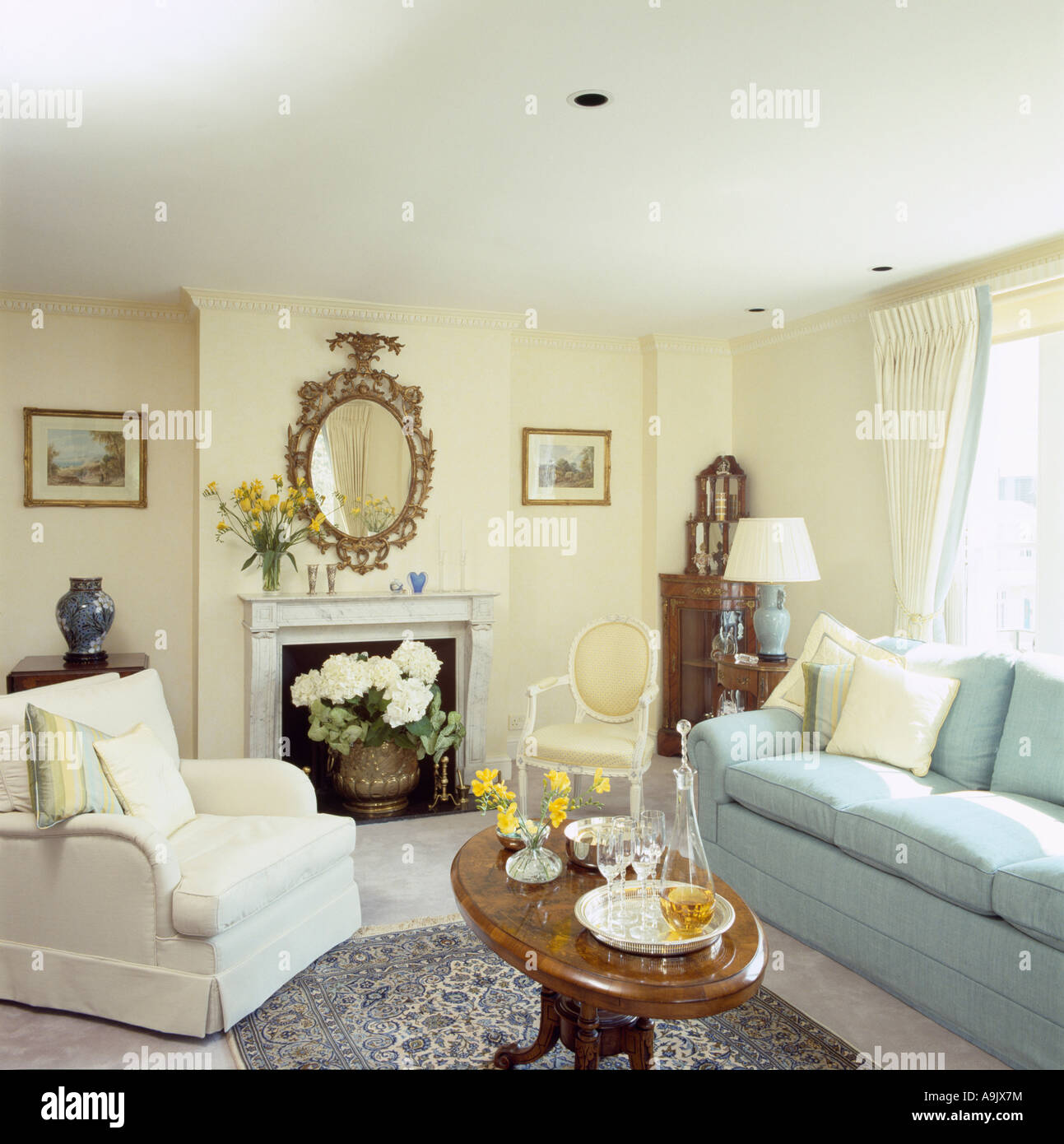 White Armchair And Pastel Blue Sofa In Pale Yellow Sitting Room With