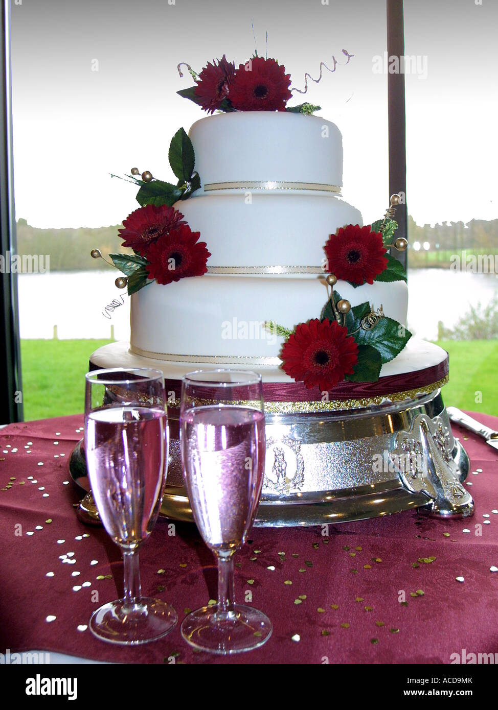 a 3 tier white wedding cake with red roses as decorations and 2 full     a 3 tier white wedding cake with red roses as decorations and 2 full  champagne glasses in the foreground