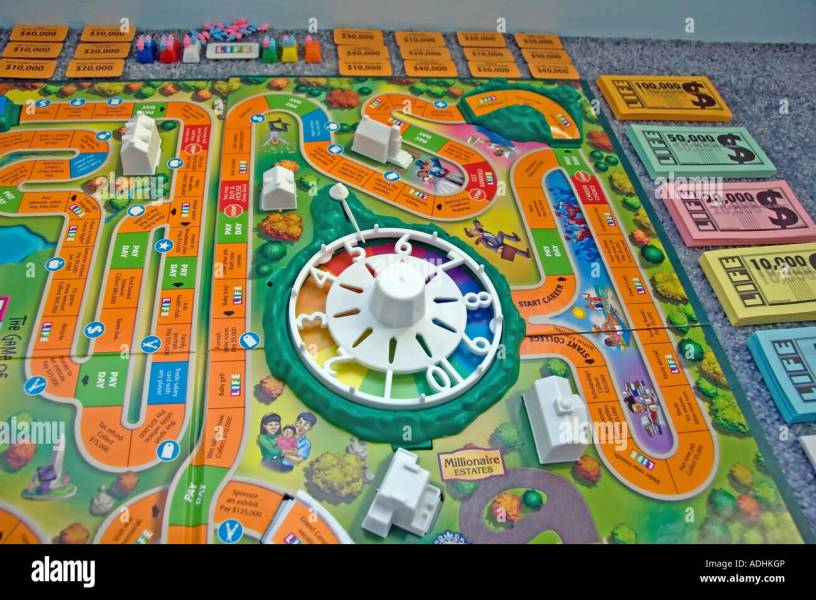 The Game of Life  by Milton Bradley  The game board   all its  Stock      The Game of Life  by Milton Bradley  The game board   all its  pieces   such as the money   cards  are all spread out