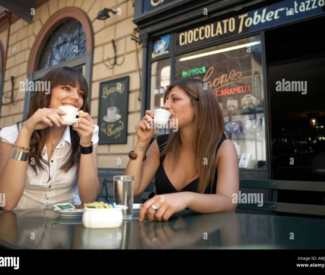 Young And Good Looking Italian Girls Drinking Coffees In Front Of Typical Italian Coffe Shop