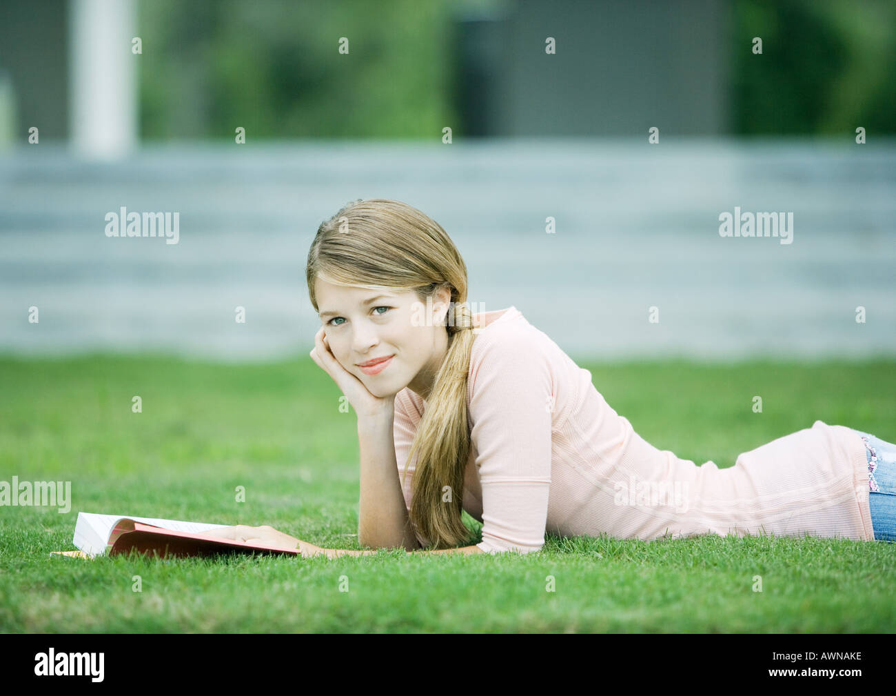 Teen Girl Lying In Grass With Book