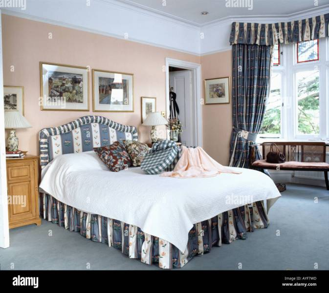 Bedroom with peach walls and bed with blue striped vallance and     Bedroom with peach walls and bed with blue striped vallance and matching  curtains