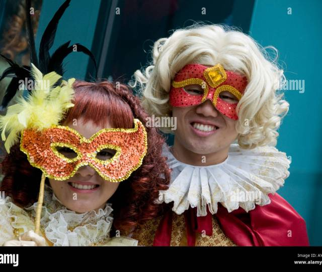 Two People In Mardi Gras Costumes And Masks