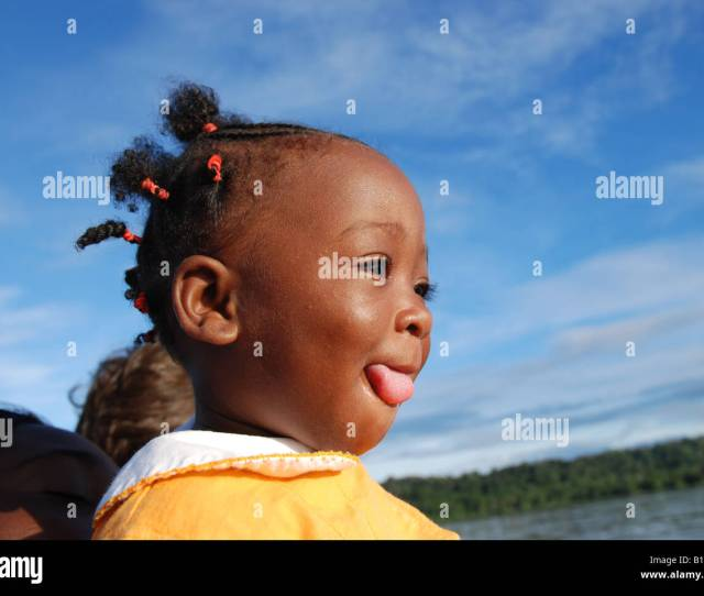Young Black Girl Tongue Out Down The River On A Canoe In South America