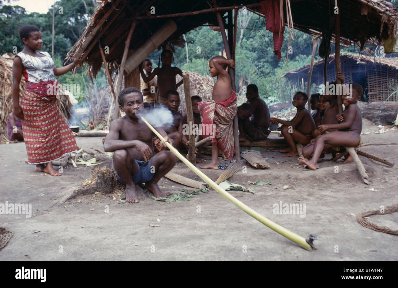 Across six countries in central africa: Congo Central Africa Ituri Forest Pygmy Group Of Nomadic Forest Dwelling Twa People With Man Smoking Hallucinogens In Long Pipe Stock Photo Alamy