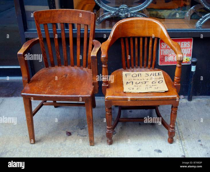 Two old wooden chairs on a city sidewalk holding a handwritten Stock     Two old wooden chairs on a city sidewalk holding a handwritten cardboard  for sale sign