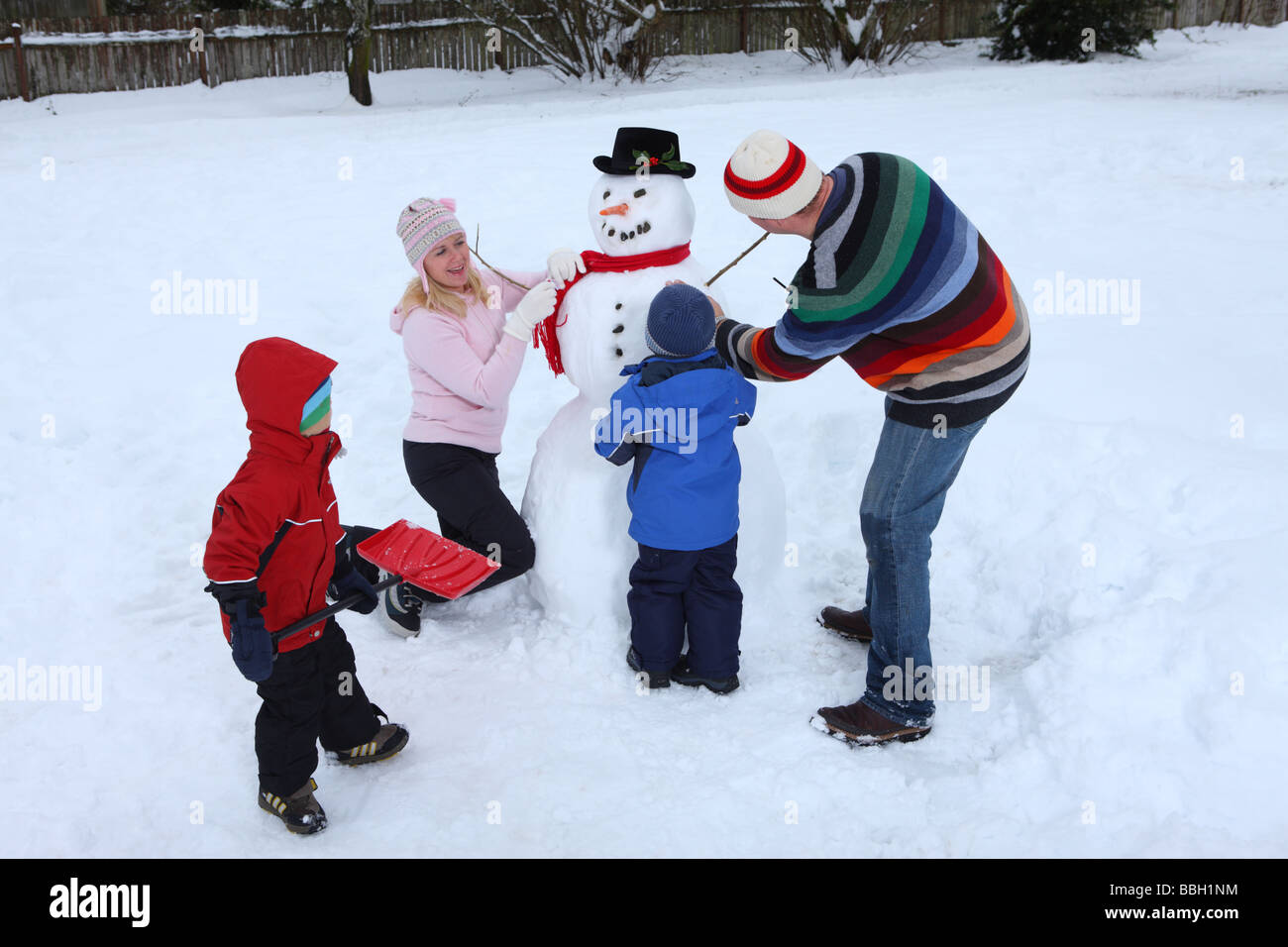 Family Making A Snowman Stock Photo