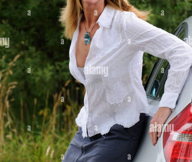 Mature Woman Wearing A White Shirt And Skirt Leaning On A Car Stock Image