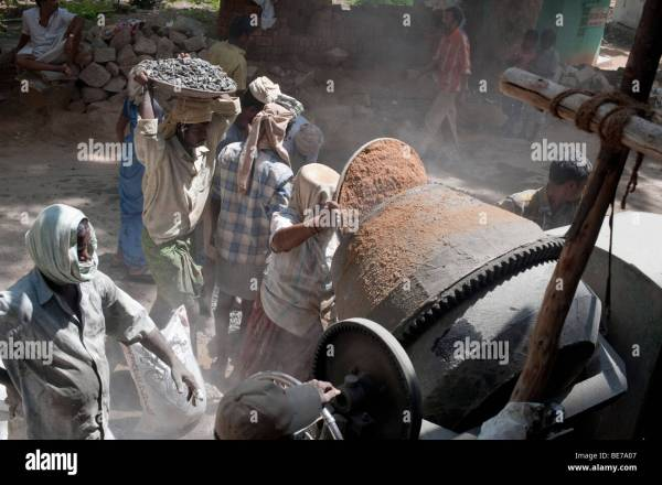 Indian construction workers mixing rock sand and cement to ...