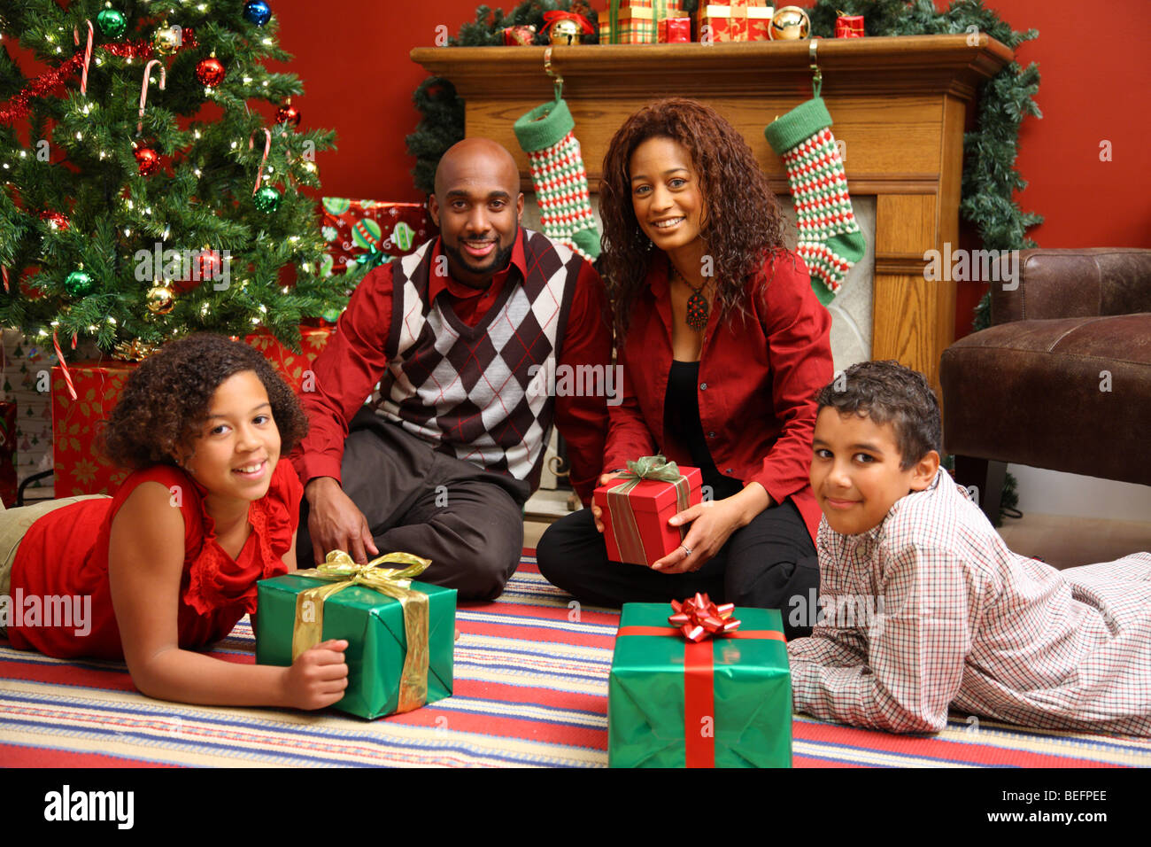 African American Family By Christmas Tree Stock Photo