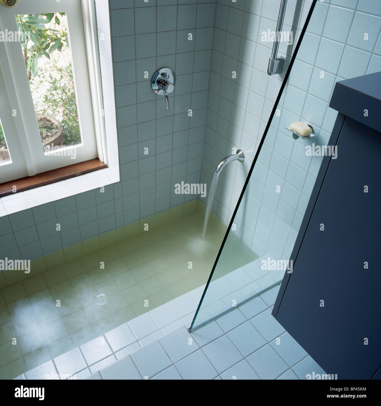 Water Pouring From Chrome Tap Into Sunken Bath With Glass Shower Stock Photo Royalty Free Image