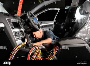 A fitter putting a wiring loom harness in a 2009 skoda