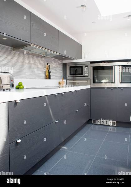 Grey ceramic floor tiles in modern white kitchen with dark gray     Grey ceramic floor tiles in modern white kitchen with dark gray fitted  cupboards and units