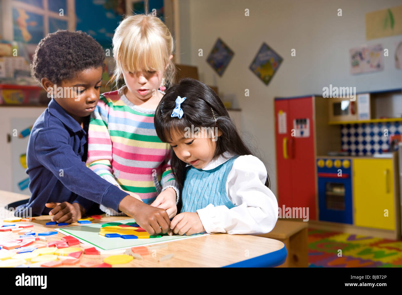 Three Preschool Children Working Together On Colorful
