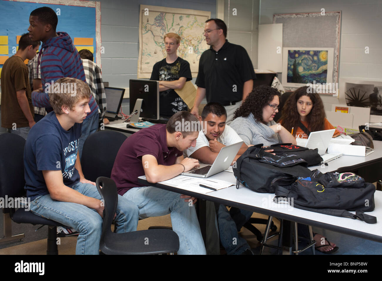 Teacher Talks To Students In Busy Classroom At Manor New Tech High Stock Photo