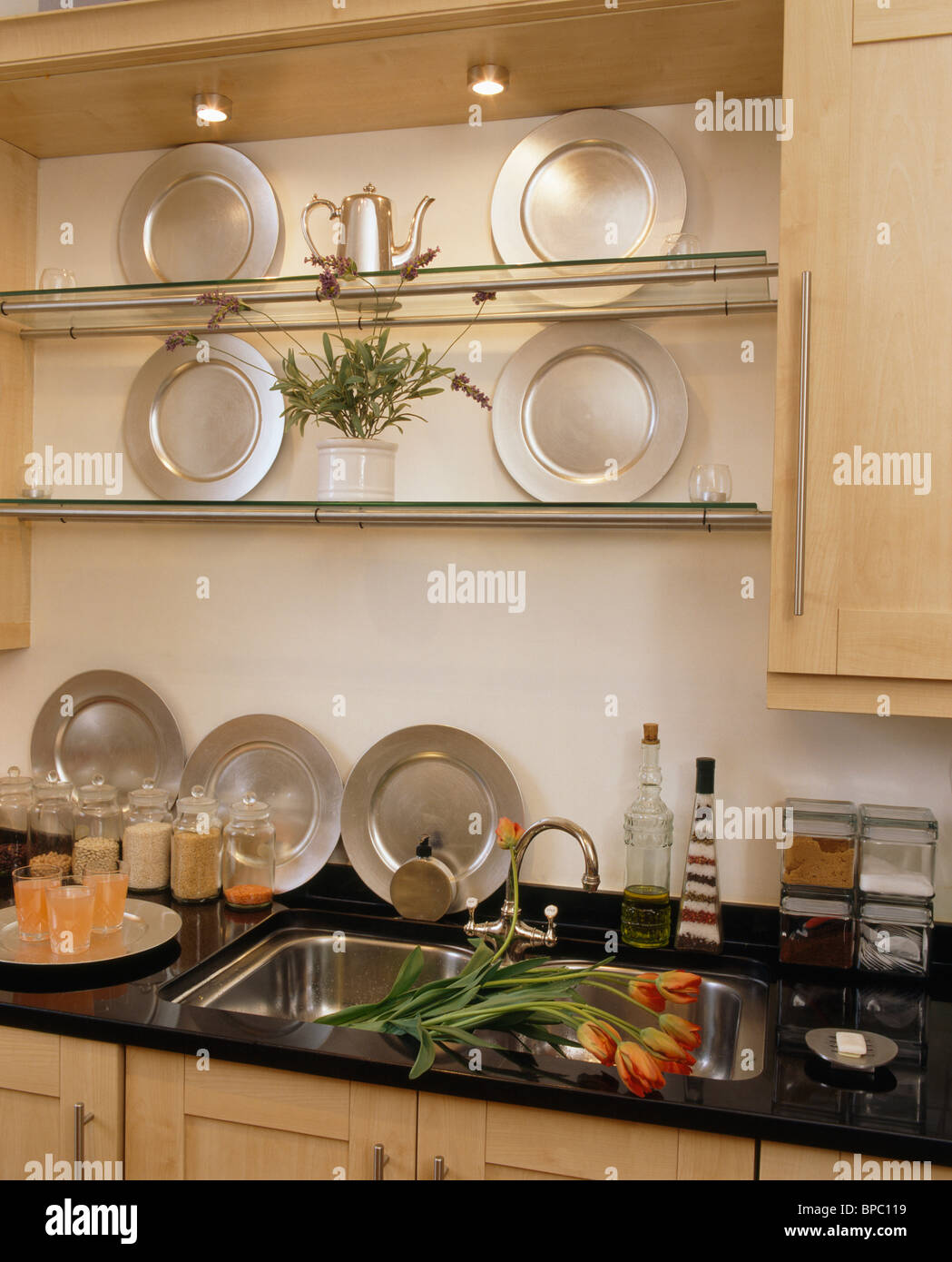 https www alamy com stock photo collection of pewter plates on glass shelves above double sink in 30997045 html