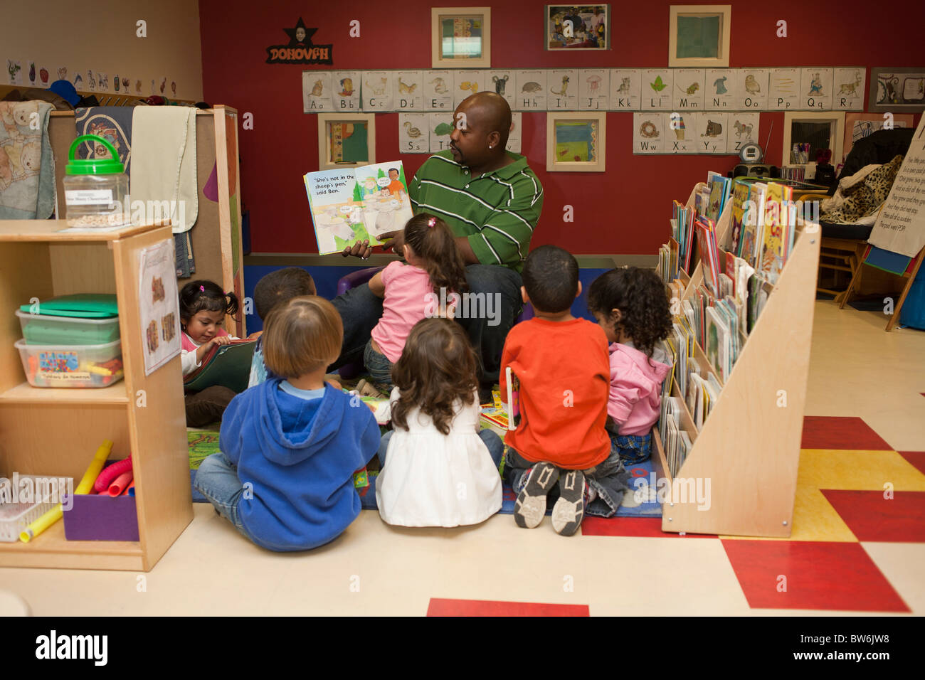 Male African American Preschool Teacher Helping Students