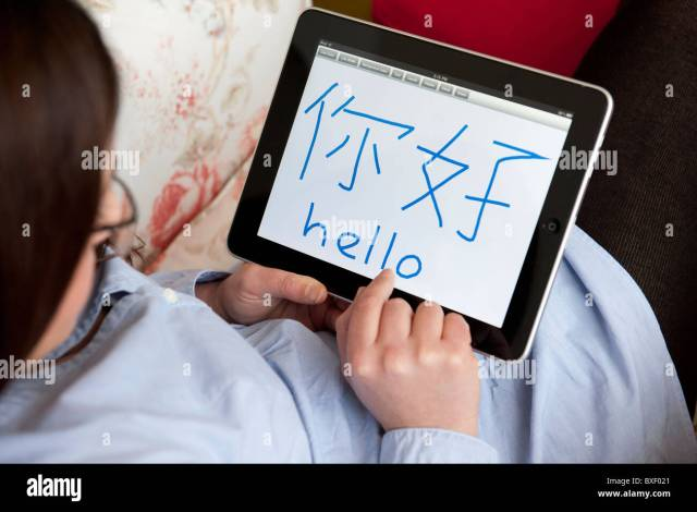 Woman learning to write Chinese characters on an iPad tablet