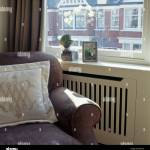 Cream Cushion On Beige Armchair In Front Of Window Above Radiator Stock Photo Alamy