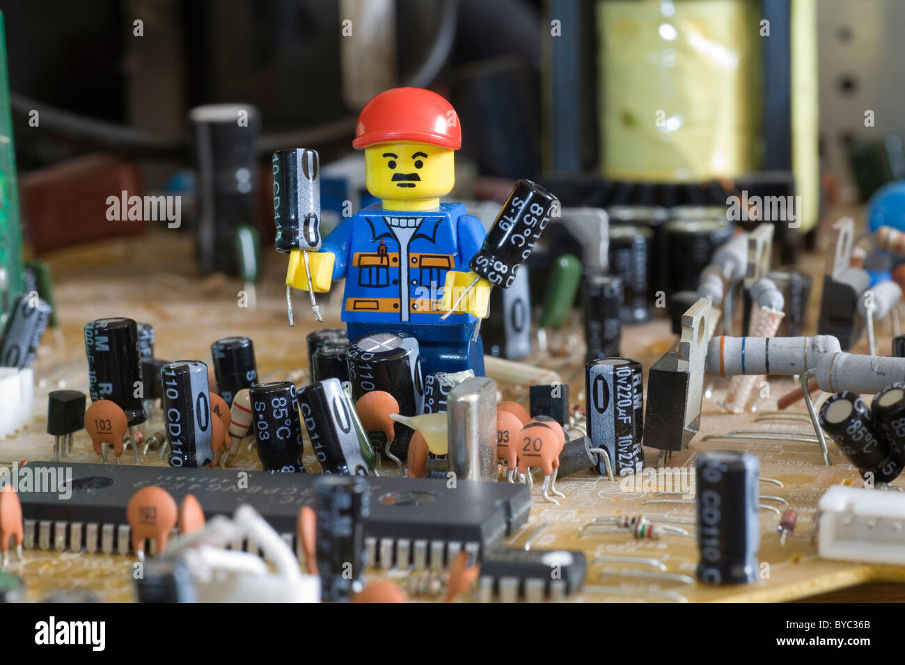Lego Engineer On Electronic Circuit Stock Photos   Lego Engineer On     lego engineer standing on an electronic circuit board holding two  electrolytic capacitors    Stock Image
