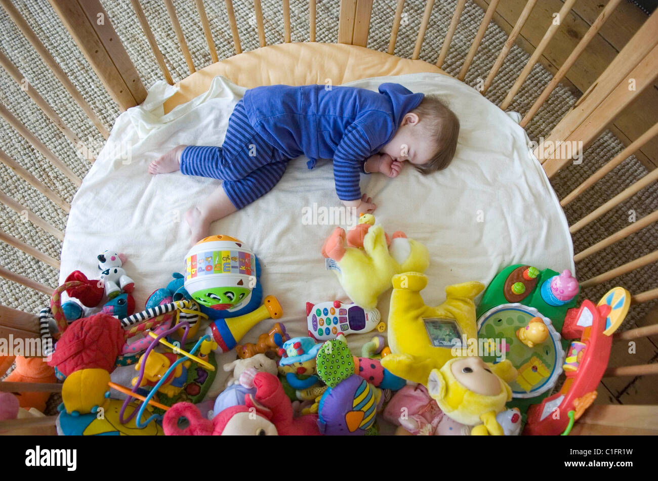 One Year Old Baby Girl Asleep In Her Playpen Surrounded By