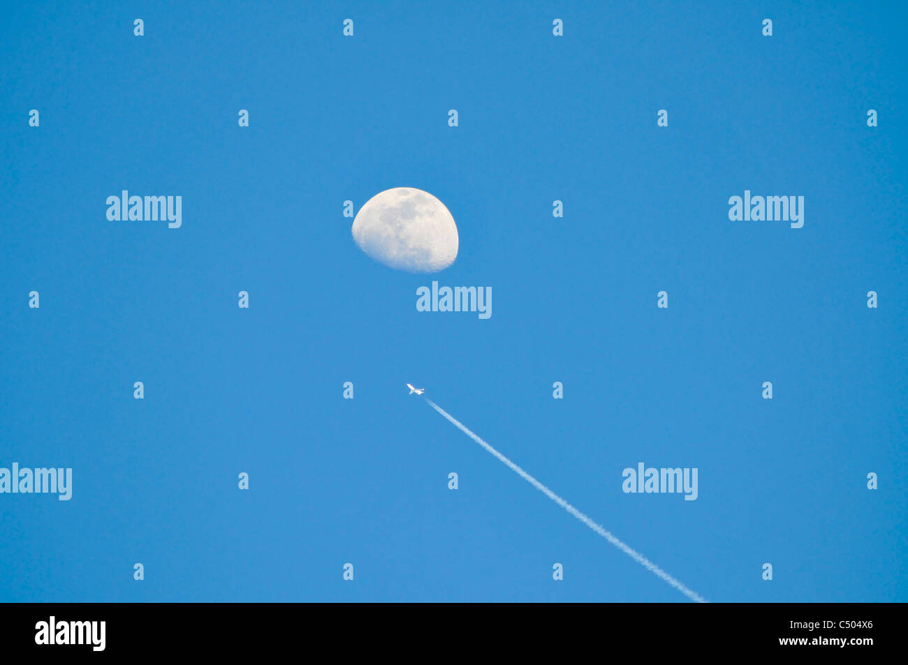 Day Time Moon On Blue Sky Background A Jet Plane Is Seen