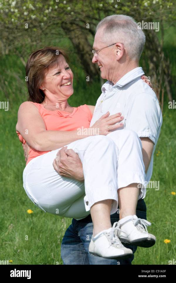 Middle-aged couple, man carrying a woman in his arms Stock ...