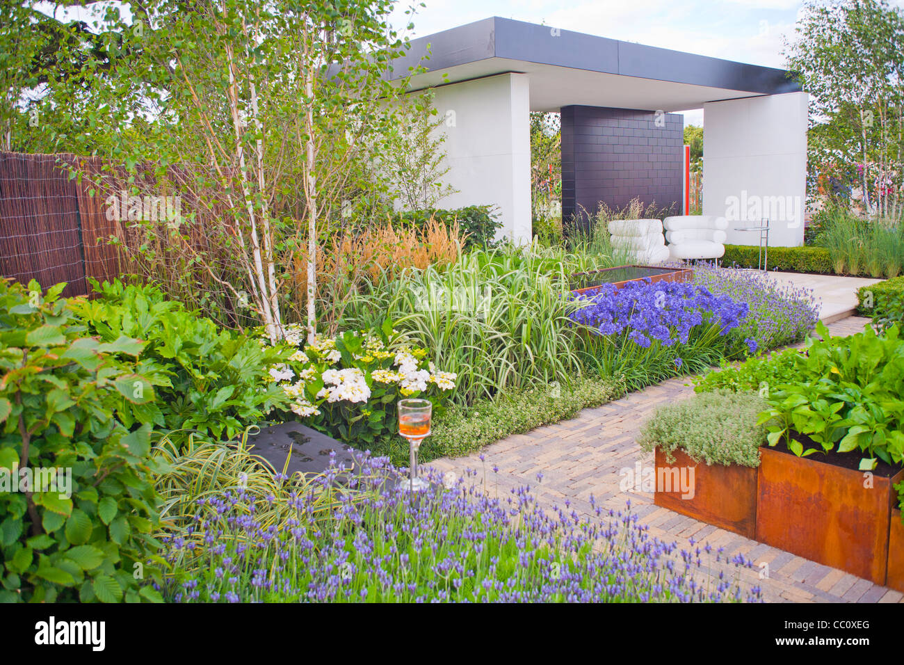 Contemporary Garden With Metal Raised Beds Paved Paths And
