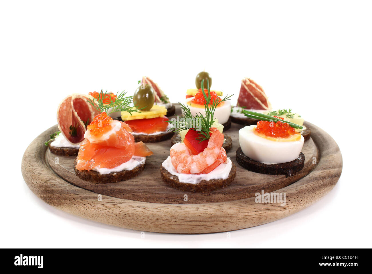 different canapes on a wooden board on a white background stock image