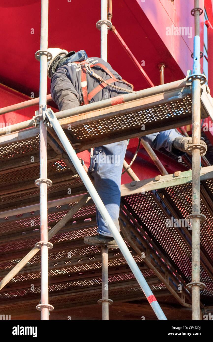 Scaffolder Wearing A Safety Harness Climbing Up An
