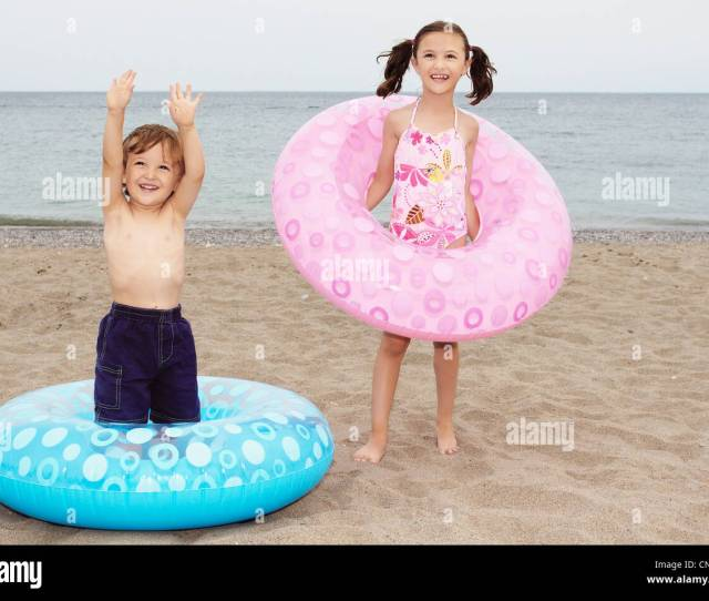 Brother And Sister Playing With Inner Tubes On A Beach Toronto Ontario