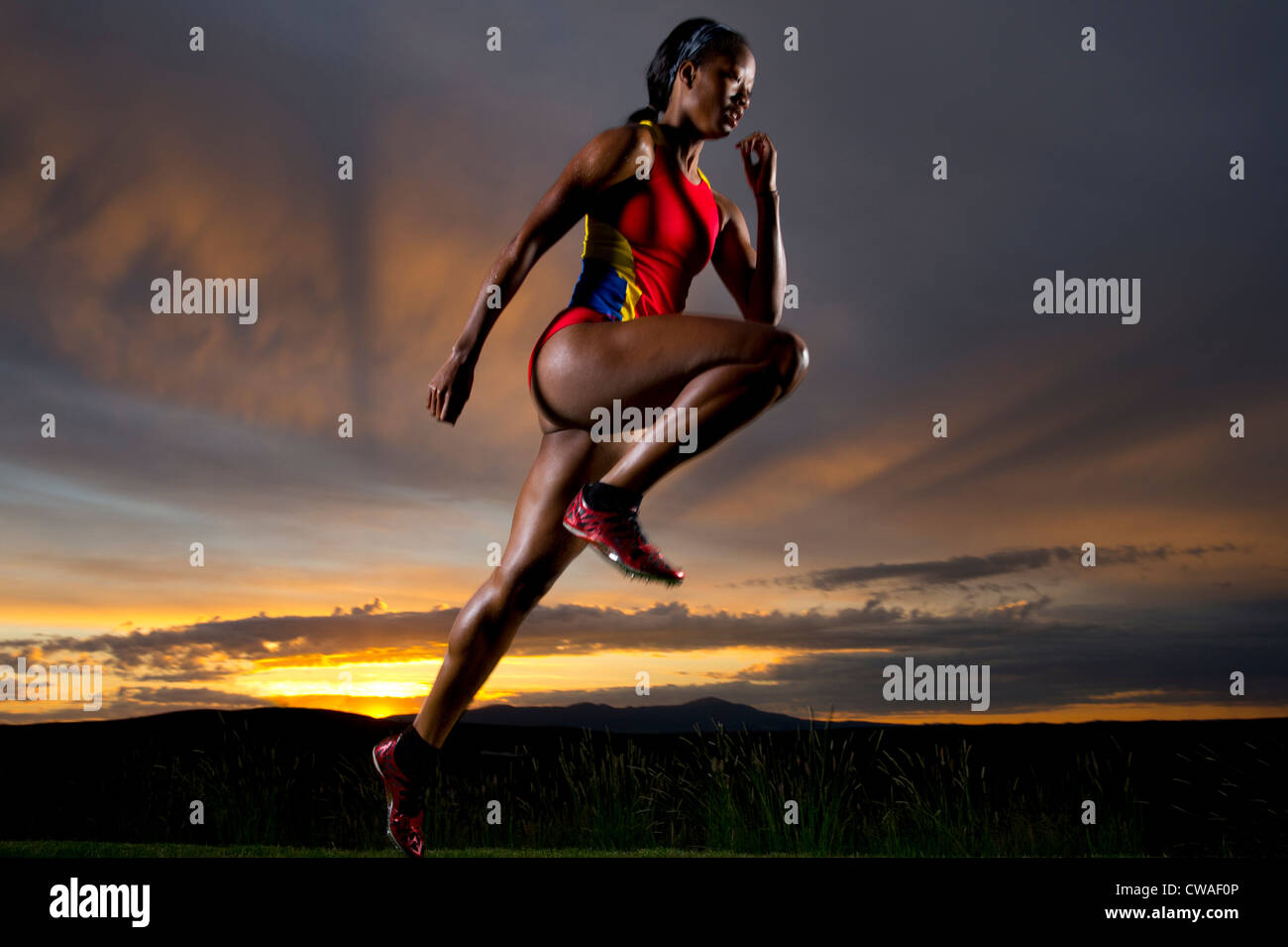 Athlete in mid air against sunset Stock Photo