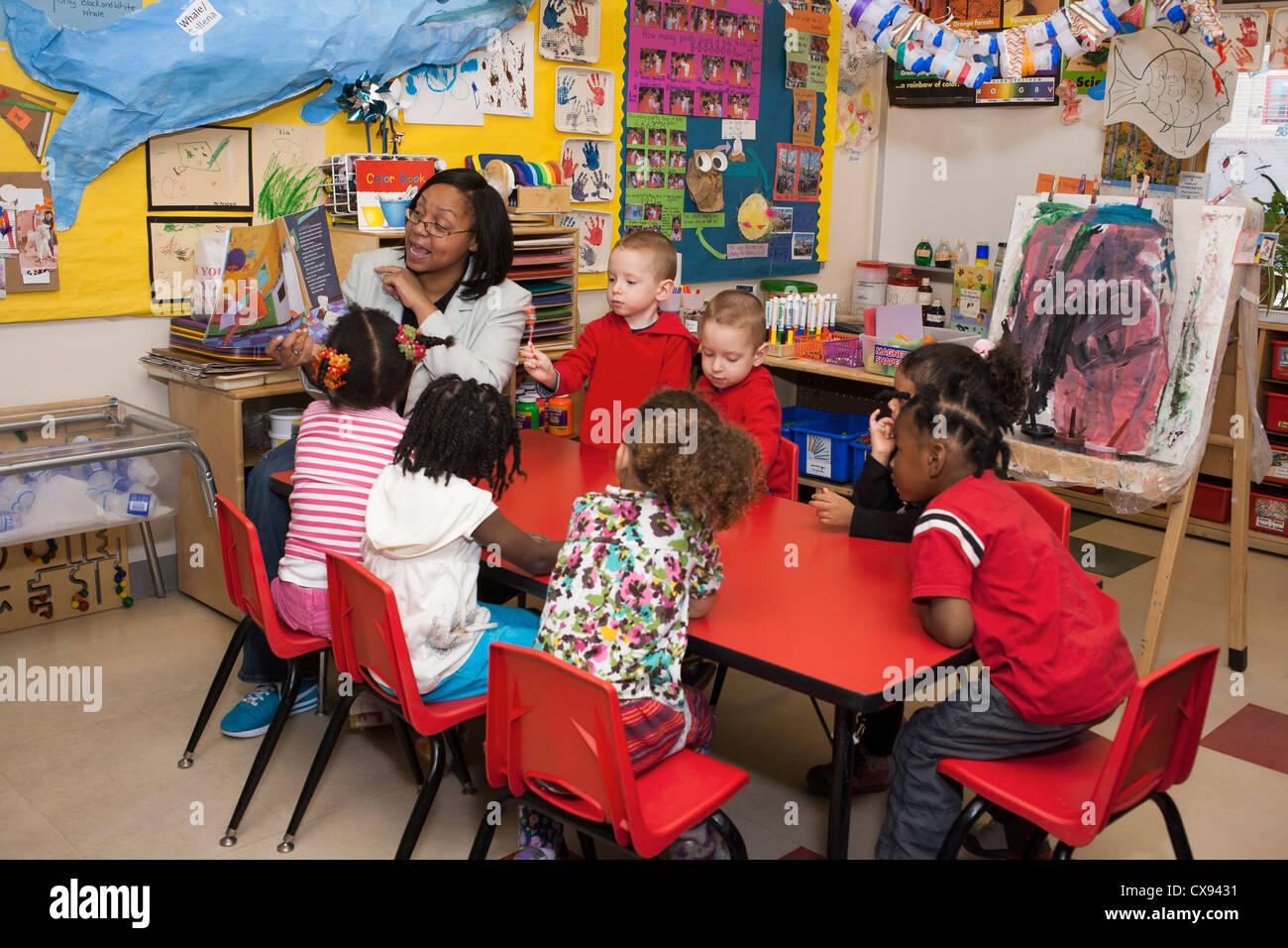 Female African American Preschool Teacher Reading To Her