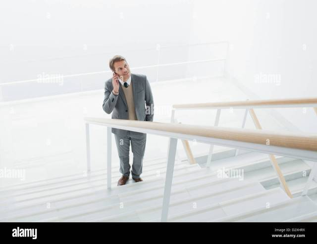 Businessman Talking On Cell Phone At Base Of Stairs