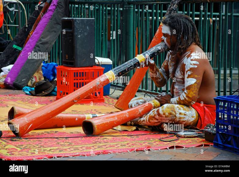 an australian aboriginal man plays a didgeridoo musical instrument