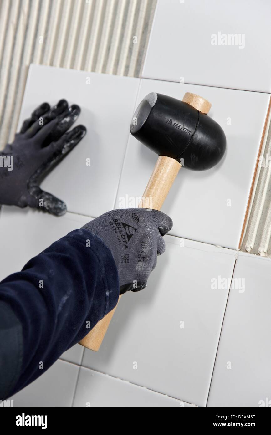 https www alamy com laying tiles on glue mortar covered wall using rubber mallet new homes image60822912 html