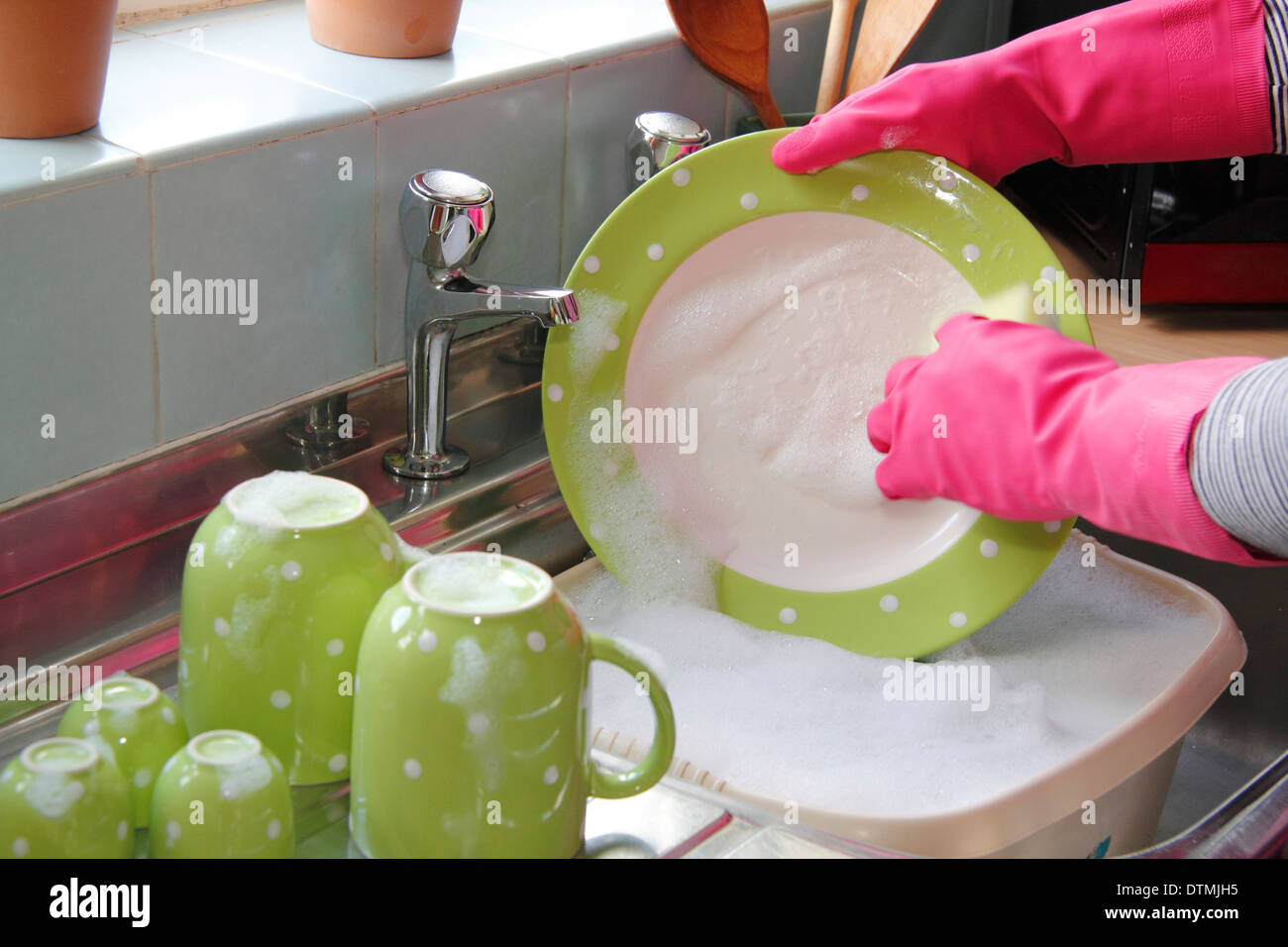 Woman Wearing Rubber Gloves Washing Up The Pots At The