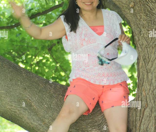 Mature Asian Woman Wearing Shorts Sitting On A Large Branch Of A Big Tree