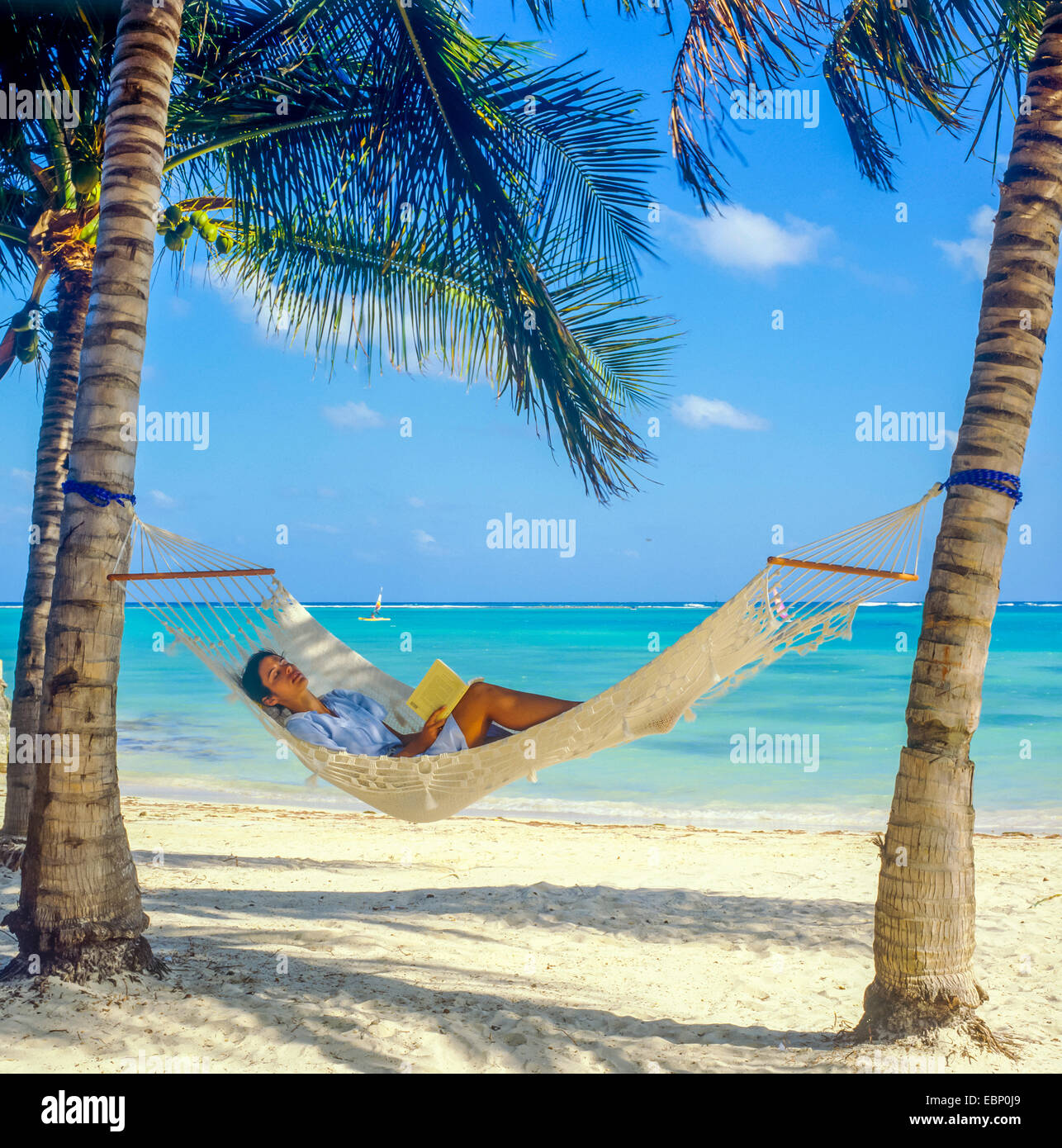 Young Woman Sleeping In Hammock Between Palm Trees On