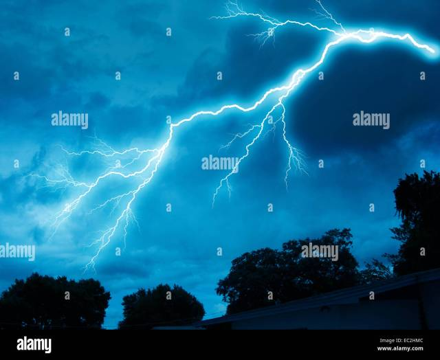 Large Lightning Bolt Above Forest At Night Stock Image